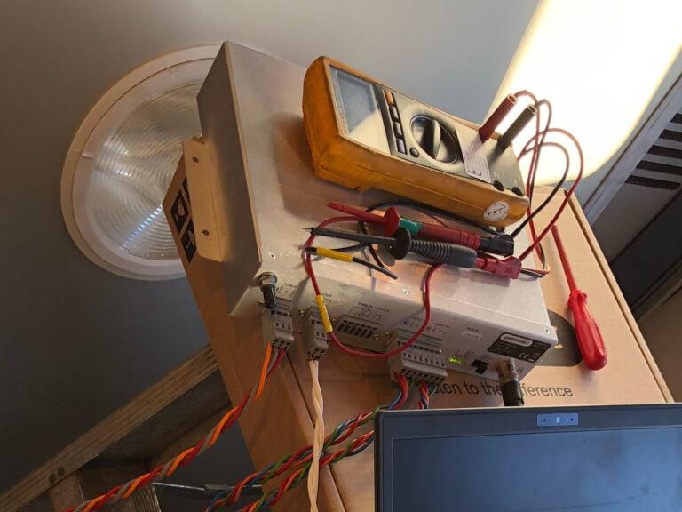 Ampetronic T14-1 Rail transporting hearing loop driver. Här mäts den och slingkabelns nivå.